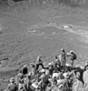 Shoemaker lecturing to astronaut group on rim crest of Meteor Crater during field trip 16-19 May 1967; USGS photo P324, F56773PR.